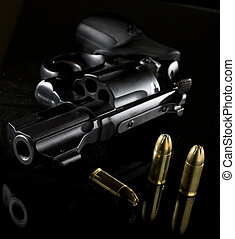 revolver and ammo - black revolver that is on a glass table...