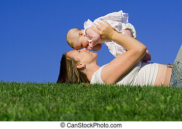 happy mother or mum playing with baby girl