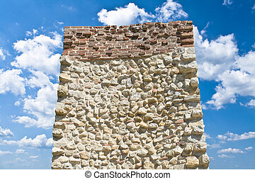 Stone monolith over blue sky with white clouds