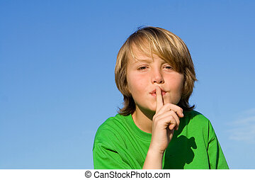 child with finger to lips to ask for quiet or silence