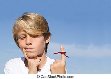 forgetful kid with string tied on finger as a reminder.