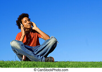 african descent youth listening to music on personal stereo...