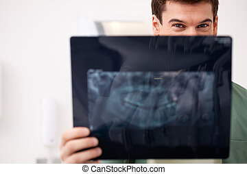 Young Male Dentist with X-ray - Young male dentist looking...