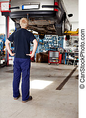 Mechanic Looking at Car - A young mechanic looking at a car...