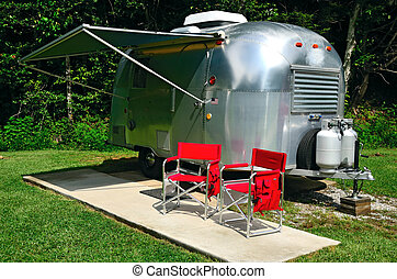 RV Camping - Classic american icon camper with two red...