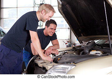 Mechanics in Auto Repair Shop - Two man mechanics smiling...