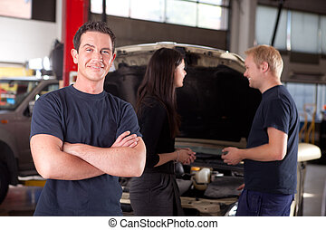 Friendly Happy Mechanic - Portrait of a mechanic looking at...
