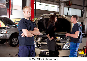 Mechanic Portrait - Mechanic looking at camera with customer...