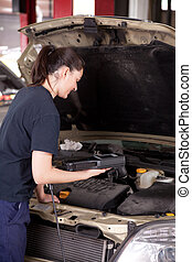 Woman Mechanic with Engine Diagnostics Tool - A happy woman...