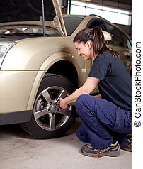 Woman Mechanic Tire Change - A woman mechanic loosening nuts...