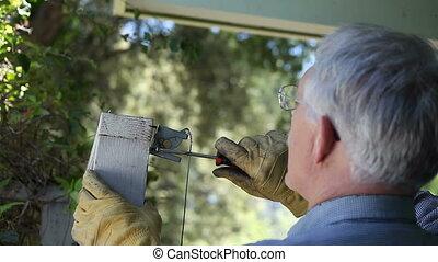 repairing gate latch - a man uses a screwdriver on a gate...