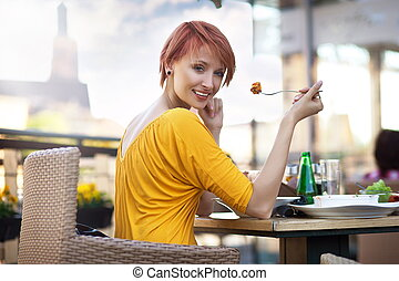 Portrait of young happy smiling woman eating lunch