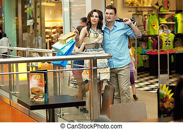 Young handsome couple having fun at shopping center