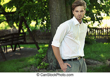 man against summer garden - Portrait of young beautiful...