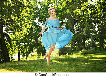 Young charming laughing woman in beautiful dress jumps on...