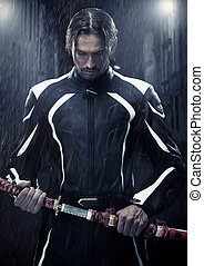 Muscular man holding samurai sword in on a rainy night