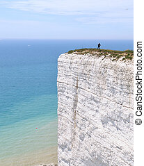 Cliff - womans figure standing on a white steep cliff in...