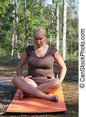 pose Sukhasana - The woman trains yoga in wood A pose...