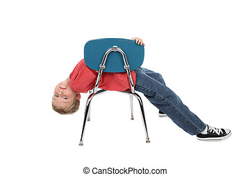 Bored child laying on chair - A young boy lays across his...