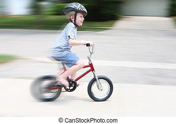 Young boy riding a bike (motion blur)
