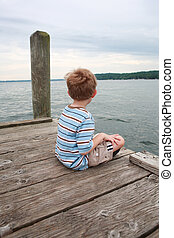 Boy sitting on a dock waiting