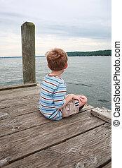 Boy sitting on a dock waiting