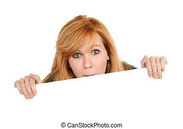 Teenage girl peeking over sign