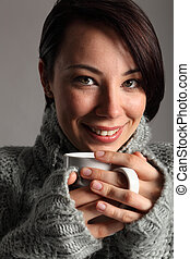 Beautiful young woman keeps warm drinking coffee