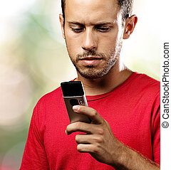 young man with mobile phone at park