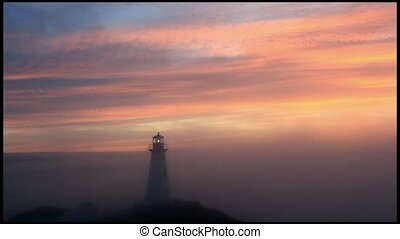 Lighthouse covered in fog at sunrise.