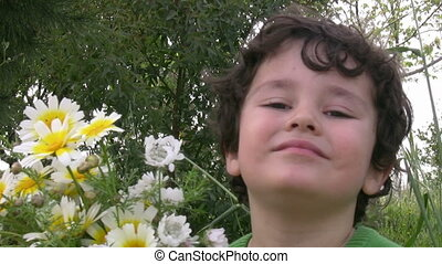 Happy Little boy picking the flowers