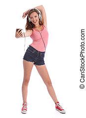 Happy long legged teenage girl has fun with music