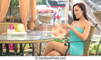 looking menu - beautiful young woman in a cocktail dress...