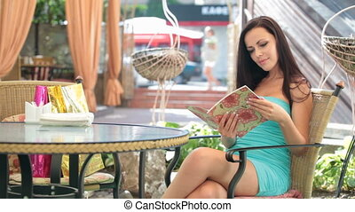 woman reading menu in a cafe