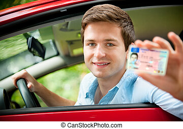 drivers license - teenager sitting in new car and shows his...