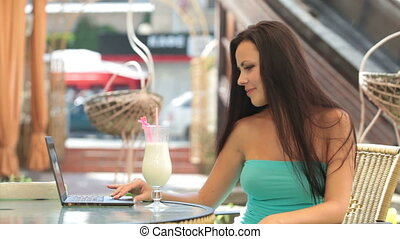 woman Using Laptop at Outdoor Cafe - Young woman Using...