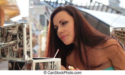 sexy girl putting lip gloss in a cafe