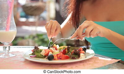 woman eating Greek salad - unrecognizable woman eating Greek...