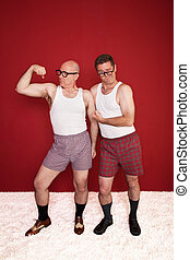 Silly Middle-Aged Men - Two middle-aged men in boxers flex...