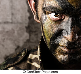 young soldier face looking straight ahead againsta a grunge...
