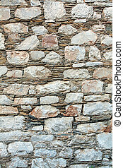 Traditional greek wall by rocks, used as background