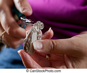 Making home made jewelry - Hands holding pliers creating...