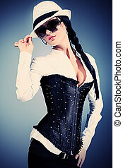 corset - Fashion photo, a model is posing over grey...