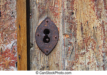 Key hole - old iron lock with key hole in a damaged wooden...