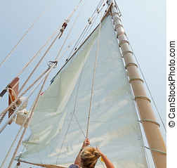Crew member raising sail on the private sail yacht - Female...