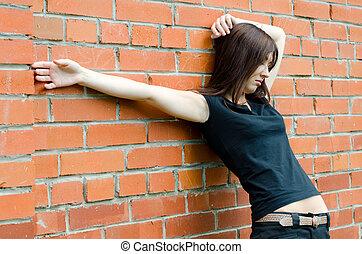 Young sad girl at brick walls - The young sad girl at brick...
