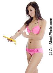 The girl in bikini with a cream