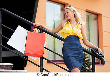 Happy shopper - Young woman with shopping bags against of...