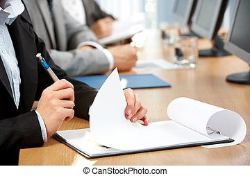 Making notes - Human hand with pen holding paper during...