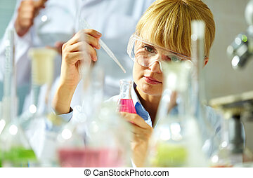 Research - Portrait of a smiling chemist working with...